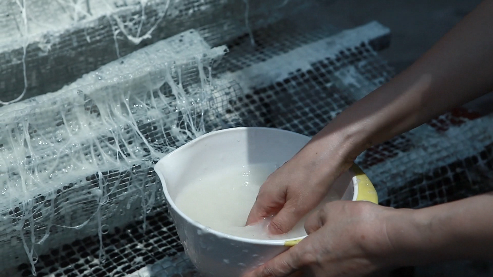 Shi Hui applying pulp to a mesh frame. Video still taken from Shi Hui directed by Chen Yi, produced by the China Academy of Art, Hangzhou.