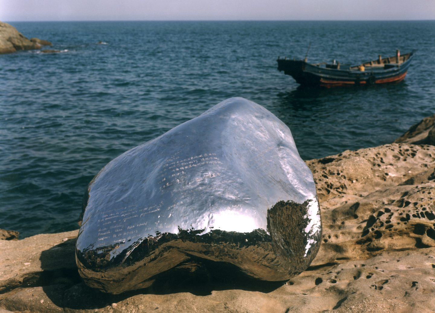 A large, shiny silver rock-like object rests on a rocky shoreline. A small boat floats in the water nearby.