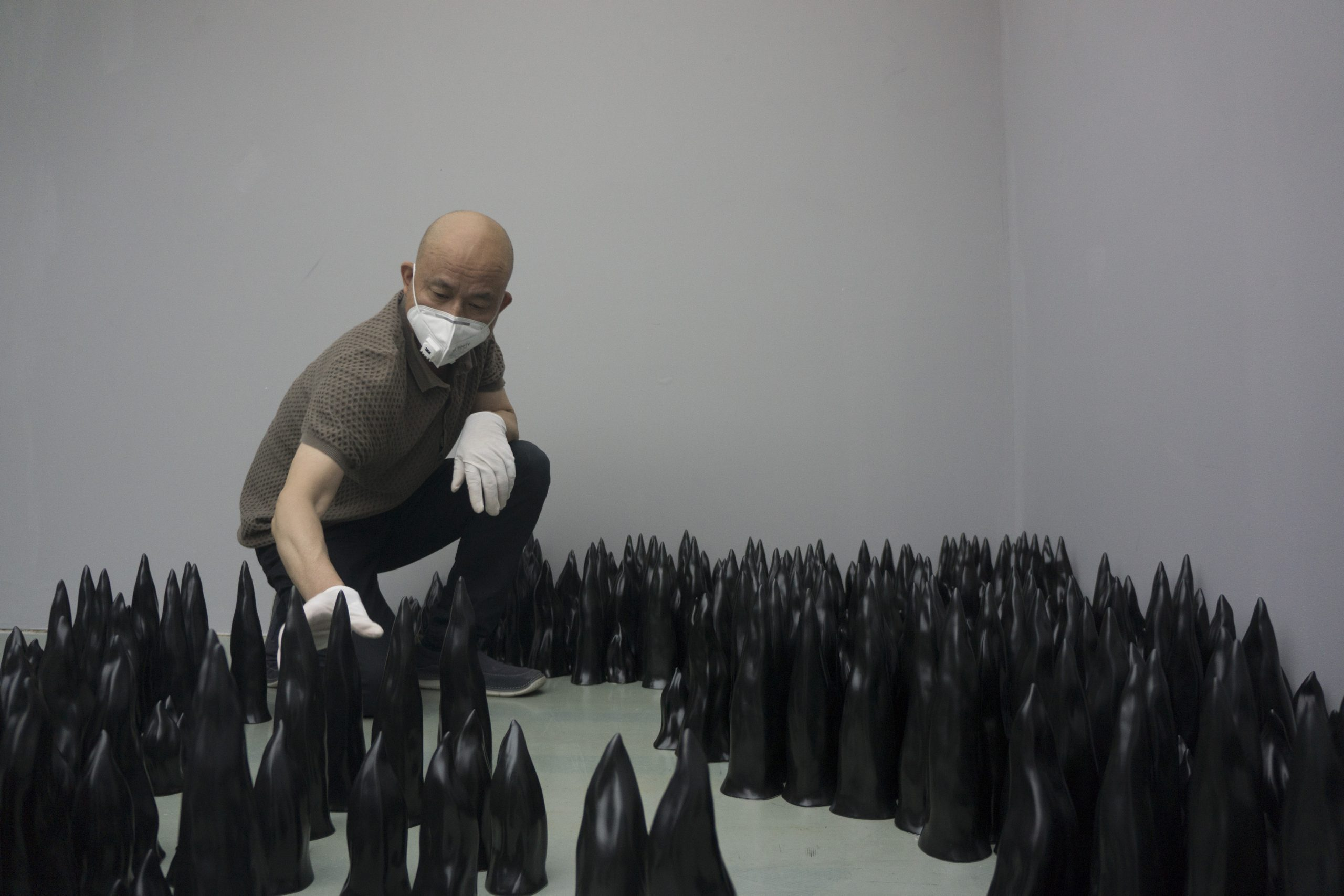 Liu Jianhua installing the work Black Flame (2017) for an exhibition at the Today Art Museum, Beijing. Photo courtesy of the artist.