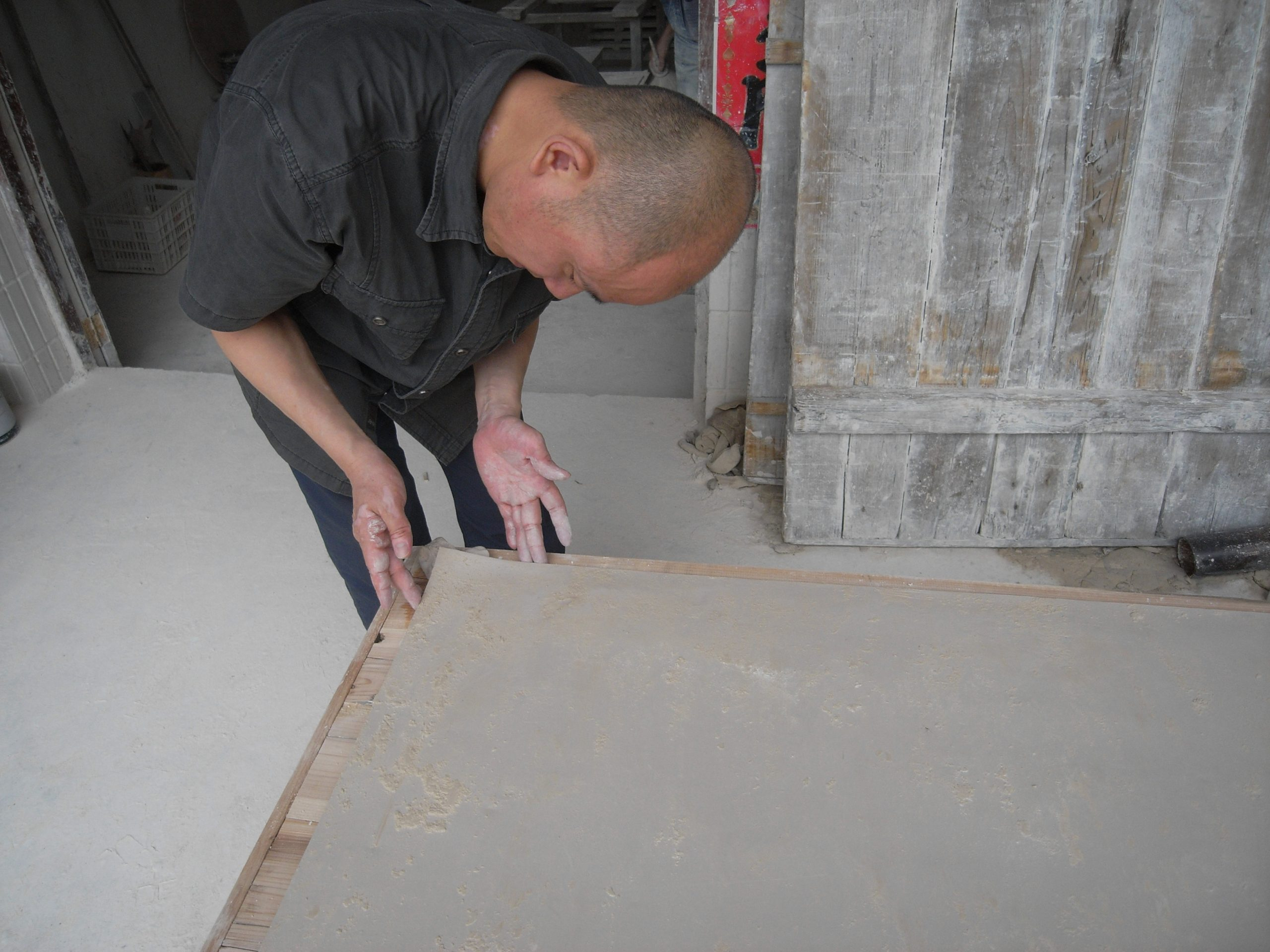 Liu Jianhua molding clay to create the slightly upturned corner of Blank Paper (2009). Photo courtesy of the artist