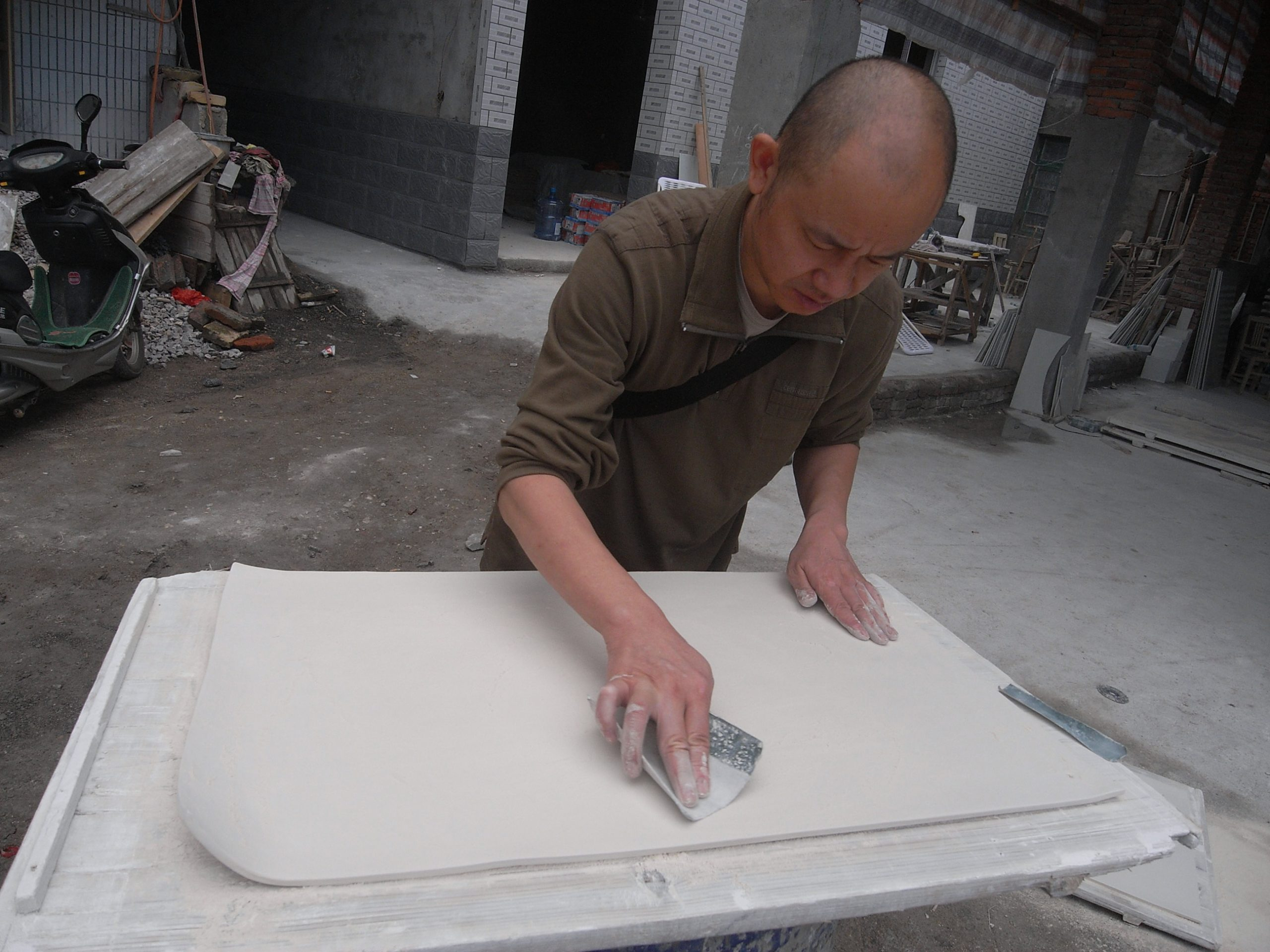Liu Jianhua smoothing out the clay surface of a work. Photo courtesy of the artist.