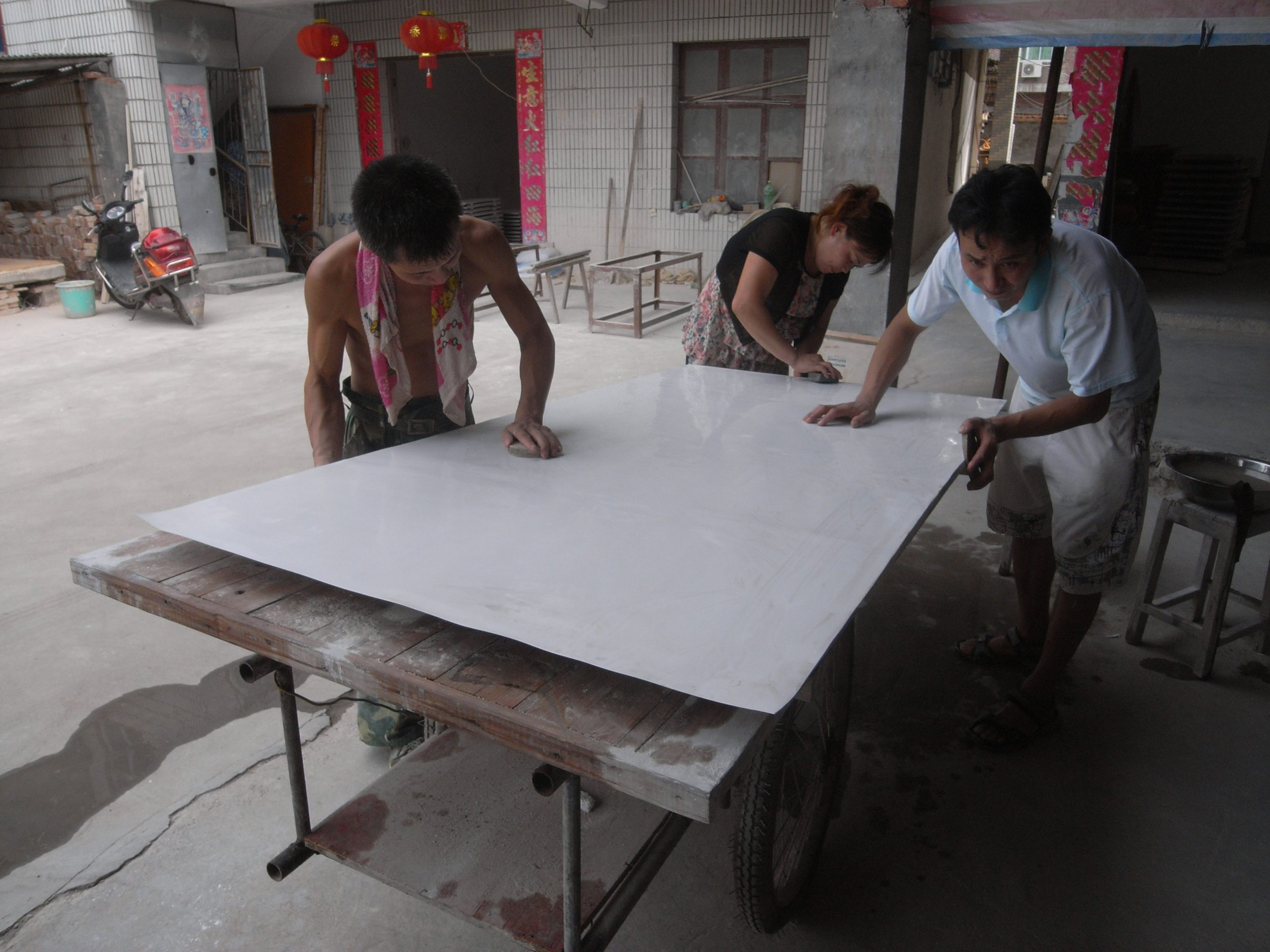 Studio assistants polishing the surface of a work. Photo courtesy of the artist.