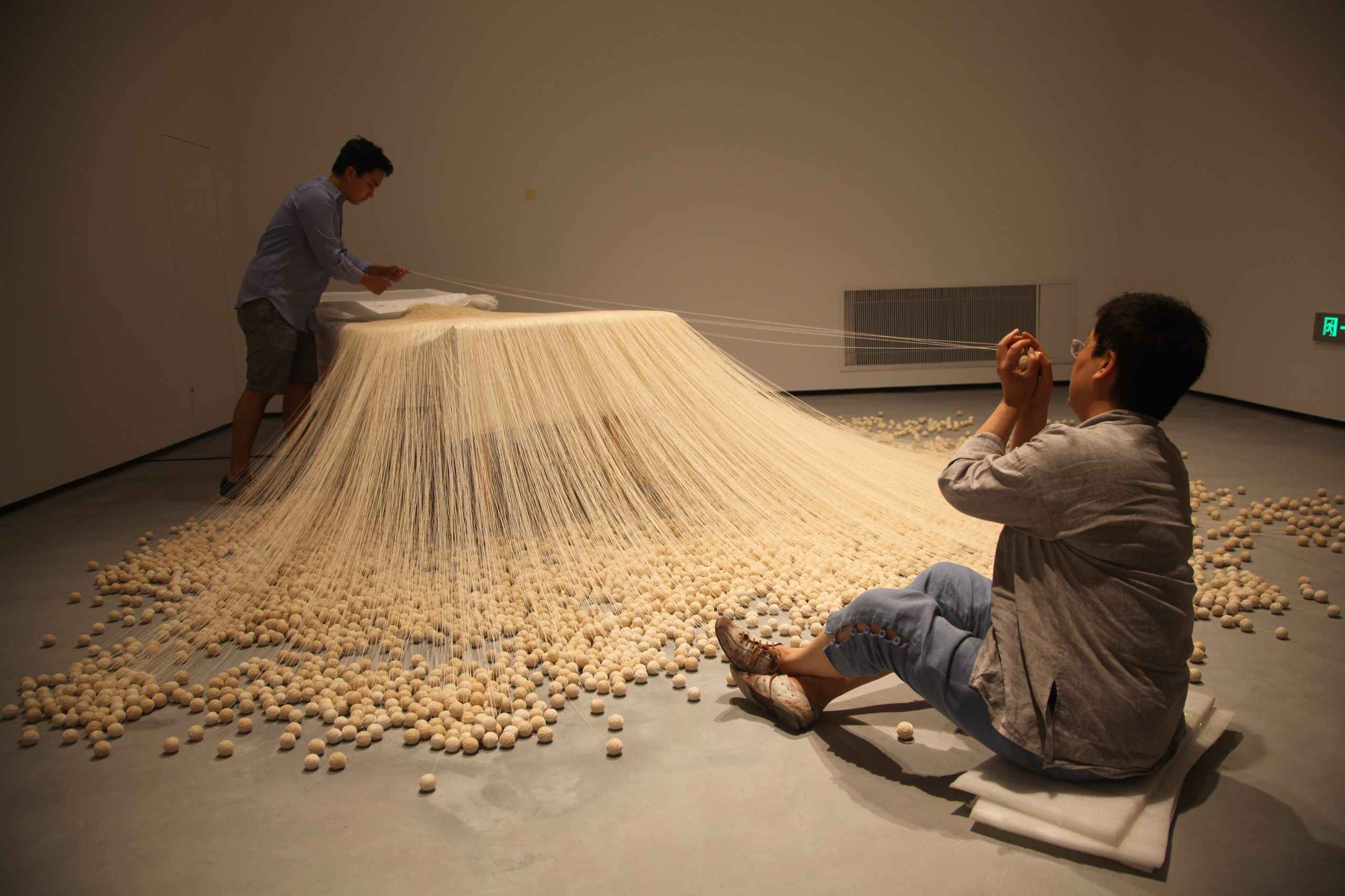 Lin Tianmiao and a studio assistant installing The Proliferation of Thread Winding (1995) for the exhibition The Civil Power, Minsheng Art Museum, 2015. Photo courtesy of the artist.