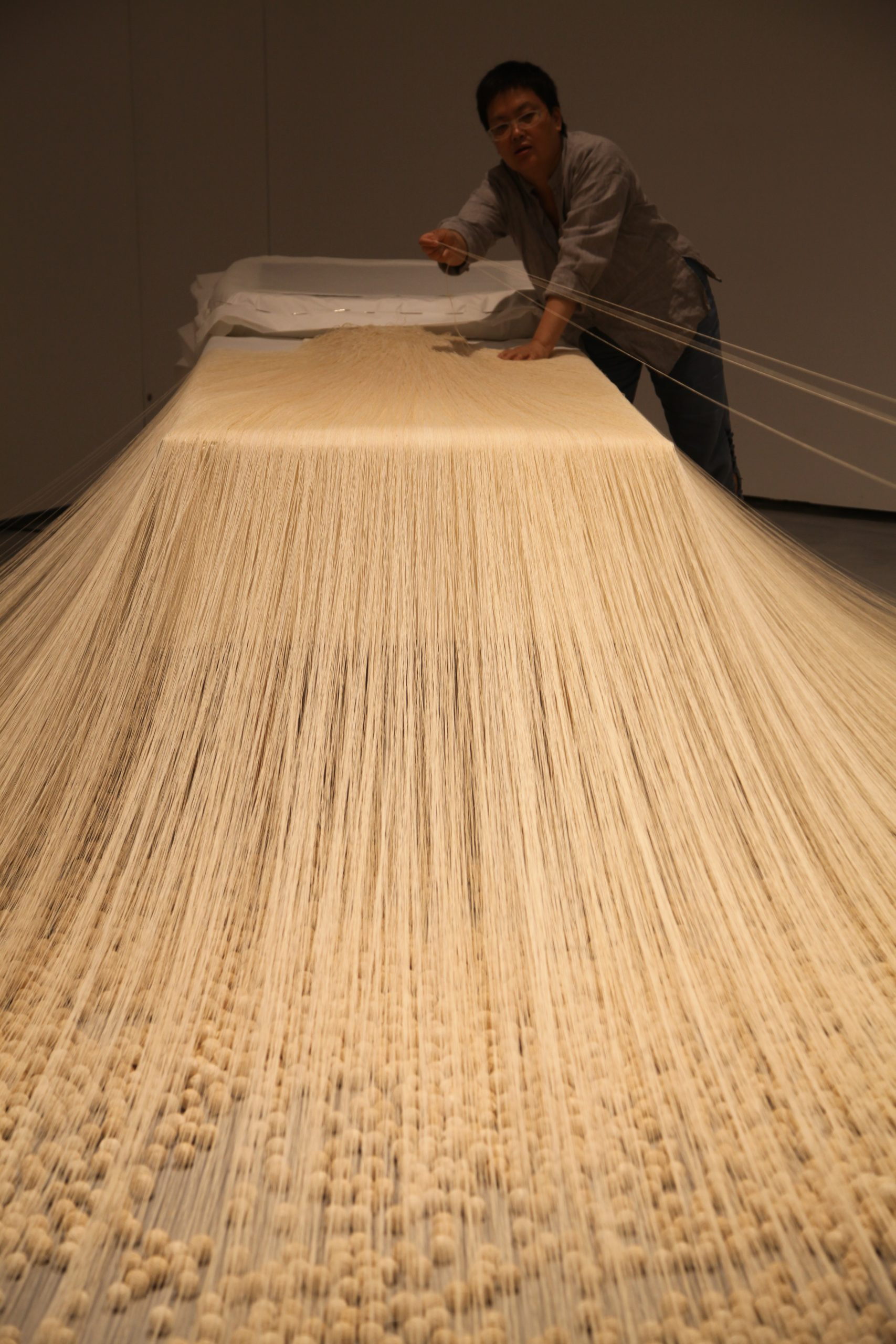 Lin Tianmiao installing The Proliferation of Thread Winding (1995) for the exhibition The Civil Power, Minsheng Art Museum, 2015. Photo courtesy of the artist.