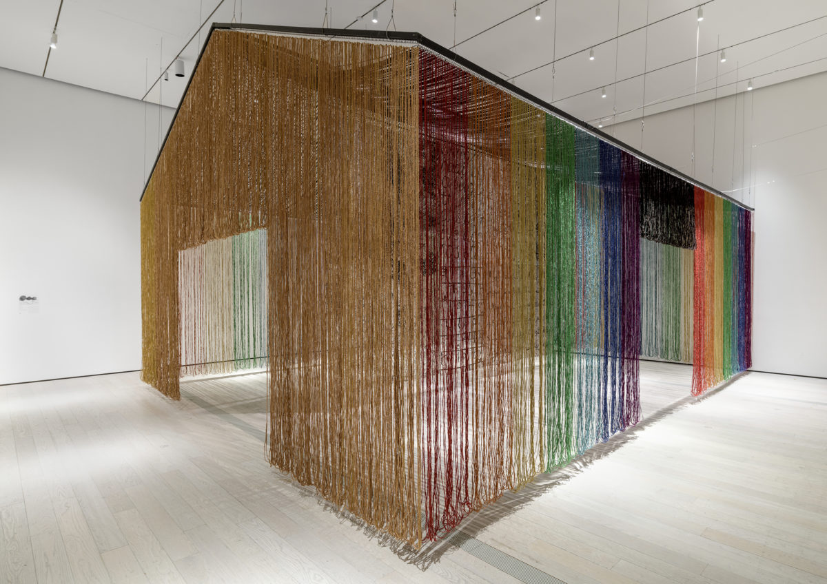 Long strands of various colors form a structure that hangs in an all-white room.