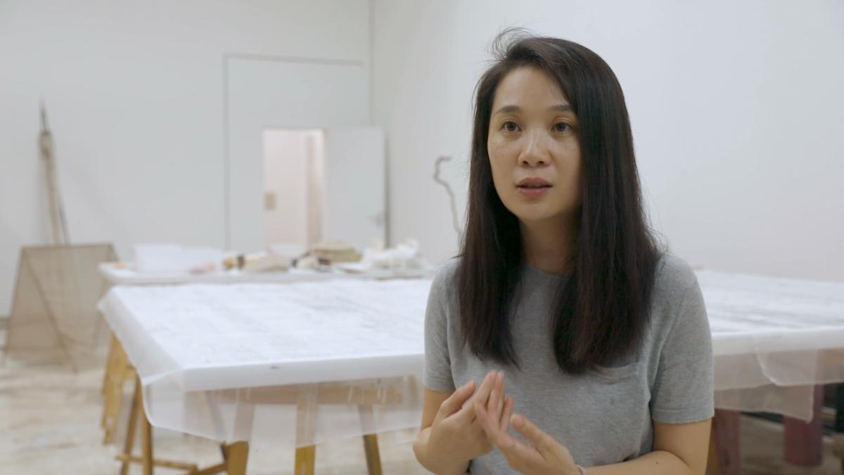 Hu Xiaoyuan seated in her studio