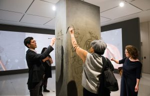 Visitors to the Smart Museum use water and brushes to write on Song Dong's Traceless Stele.